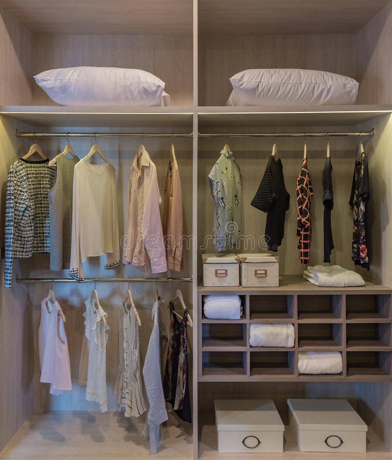 Modern closet with clothes hanging on rail. Wooden wardrobe, walk in closet interior design royalty free stock photography