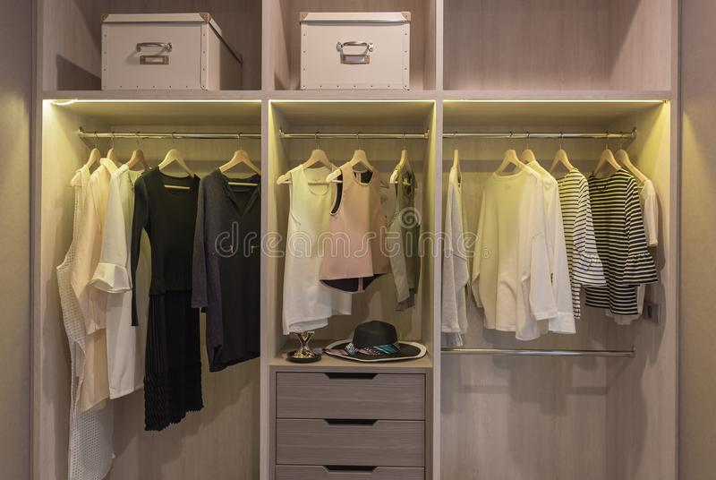 Modern closet with clothes hanging. On rail, wooden wardrobe, walk in closet interior design royalty free stock images