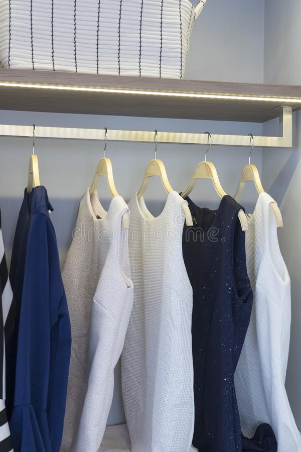 Modern closet with row of cloths hanging. In white wardrobe stock image