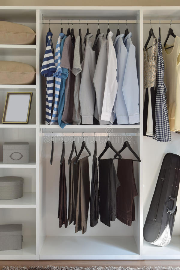 Modern closet with row of cloths hanging in white wardrobe stock image
