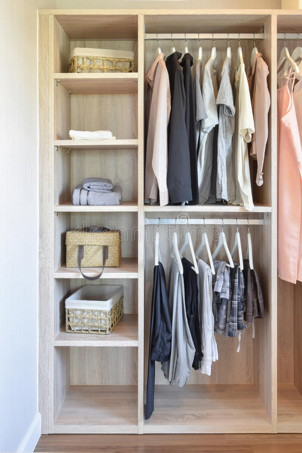 Modern closet with row of cloths hanging in wooden wardrobe stock image