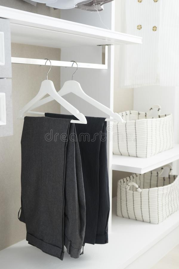 Modern closet with row of pants hanging. In white wardrobe royalty free stock photos