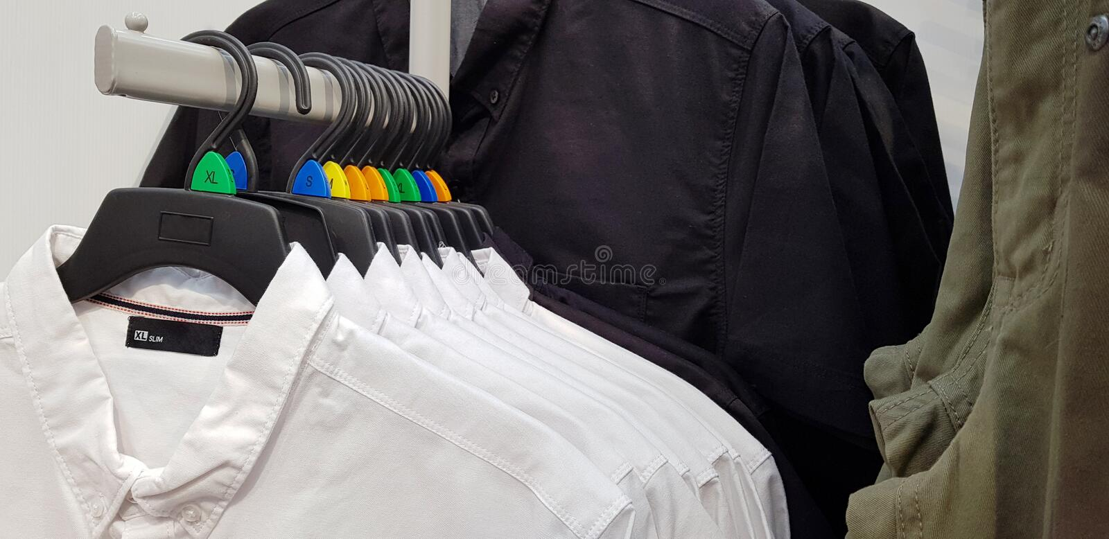 Modern clothes in a shop on a hanger. Shirts and sweaters of different colors and denim for youth. Clothes of different styles on stock image