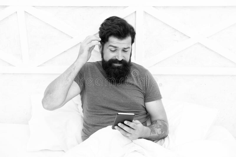 Modern communication. Checking social networks. Cellular communication. Modern guy talking on smartphone in bed stock photo