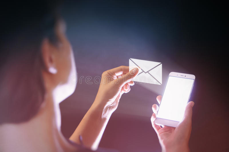 Modern communication technologies. Image of a woman with a smartphone in her hand. She receives an email. Online mail, correspondence, feedback, reporting stock images