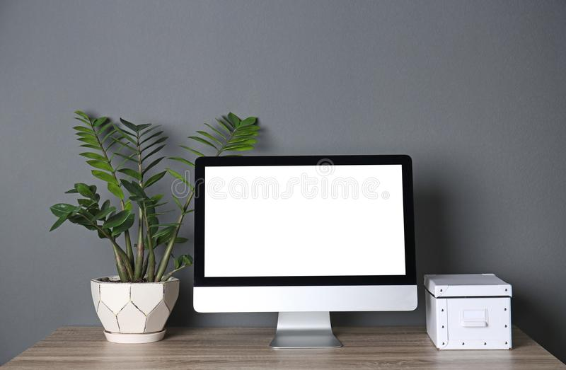 Modern computer monitor on table against wall. Mock up with space for text. Modern computer monitor on table against gray wall. Mock up with space for text royalty free stock photography