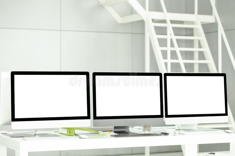 Modern computers have blank white screens and business documents. Are placed on the table in a luxury office stock images