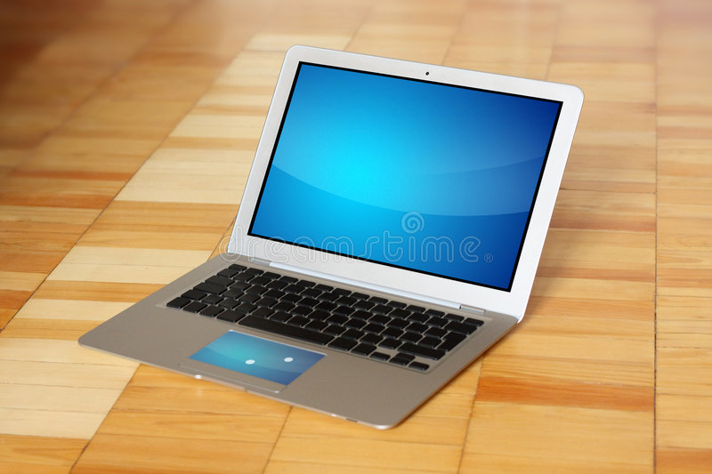 Modern conceptual laptop computer on wooden floor stock image