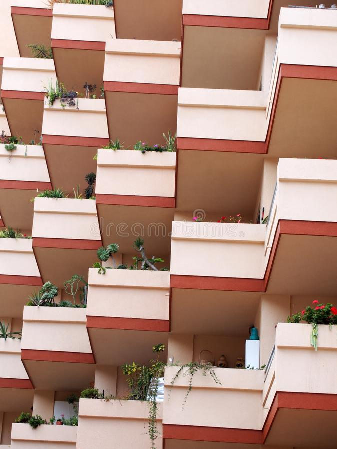 Modern concrete pink apartment blocks with balconies and plants. Modern concrete pink apartment blocks with balconies and window box plants royalty free stock photography