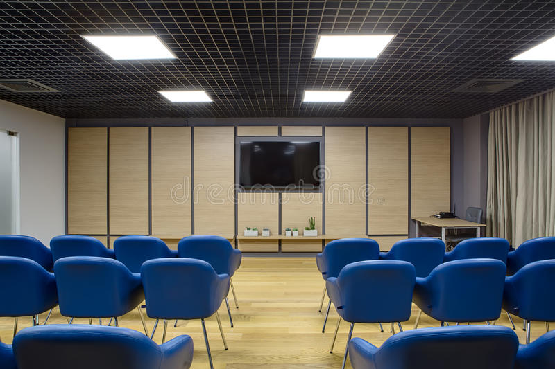 Modern conference hall. Lecture room in a coworking. There are a lot of blue chairs. Background wall is dark gray with wooden panels and TV on it. There are stock images