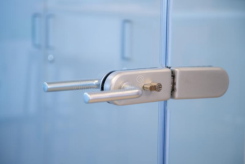 Modern, contemporary glass door lock handle in modern business office stock images