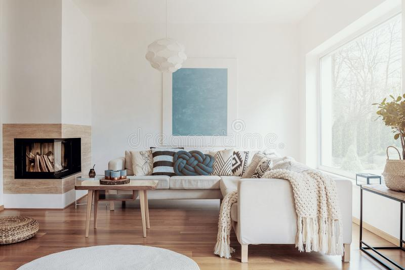 Modern corner fireplace in a sunny, peaceful living room interior with white walls and cozy pillows and blankets on a beige sofa. Concept stock photo