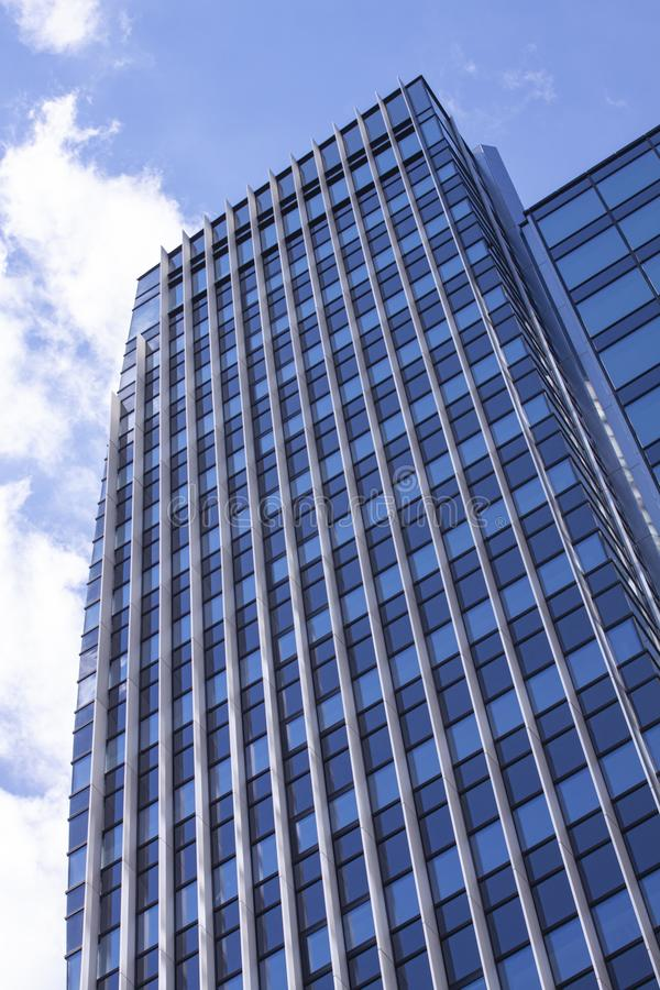 Modern corporate highrise office building reflecting sky with clouds seen from below. Image stock photography