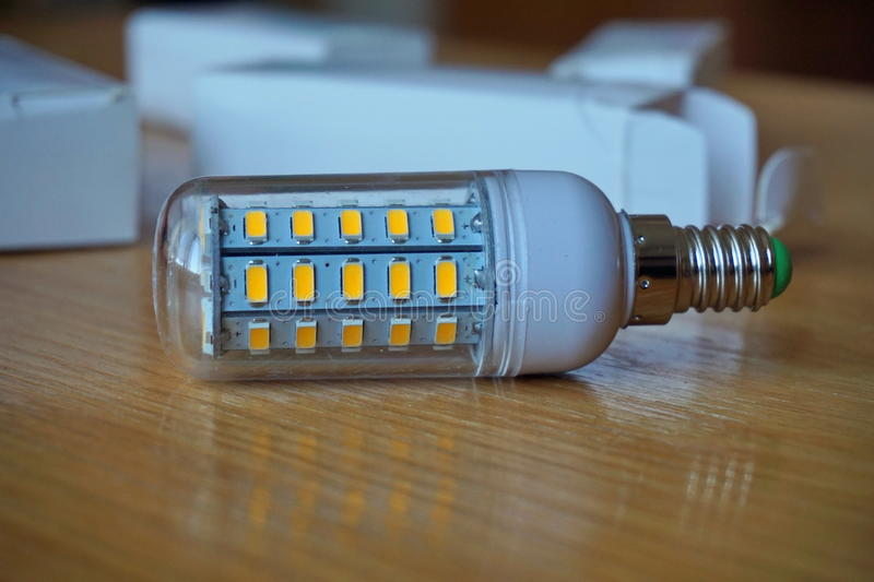 Modern cost-saving ecological LED (Light Emitting Diode) bulb in blue color stock photography