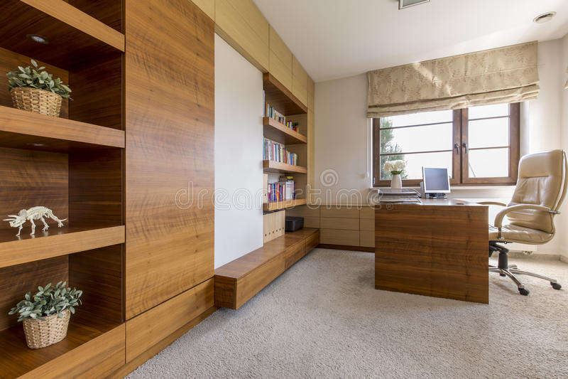 Modern and cosy office room in a luxurious house. Bright office room in a house, with a leather swivel chair and a set of modern wooden furniture stock photos
