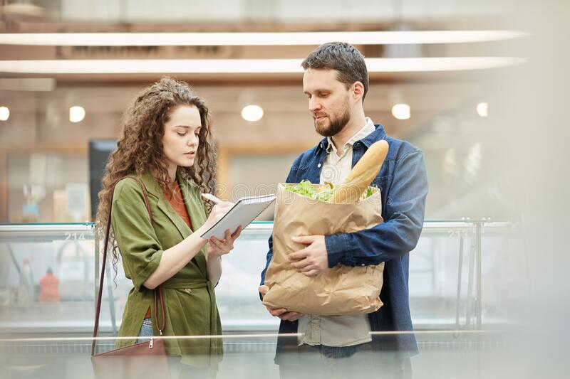 Modern Couple Reading Shopping List in Supermarket stock photos