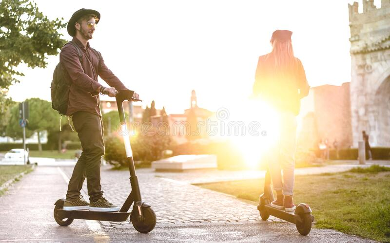 Modern couple using electric scooter in city park - Milenial students riding new ecological mean of transport - Green eco energy stock image