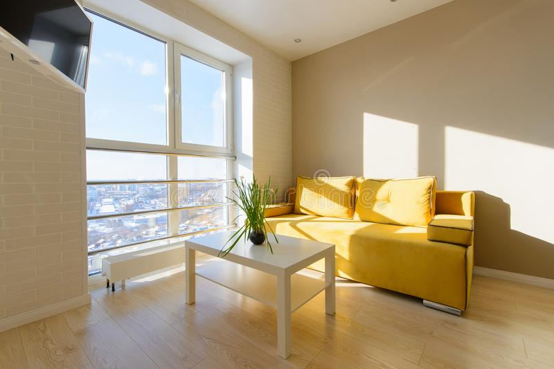 Modern cozy apartment interior, living room with yellow sofa, white coffee table and tv on wall, panoramic window with. Beautiful view to the city stock images