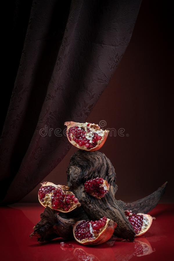 Modern creative food photography - pieces of ripe pomegranate. Shooting in low key style stock image