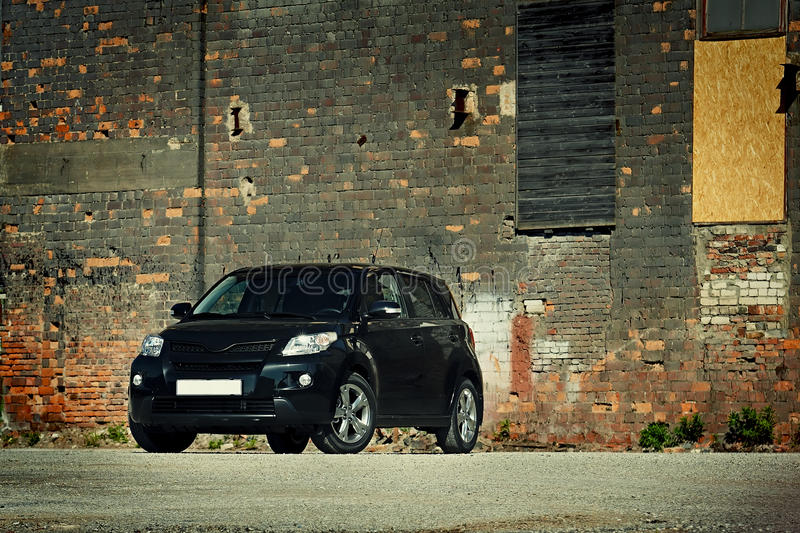 Modern crossover. 3/4 view of modern crossover vehicle near old brick wall royalty free stock photos