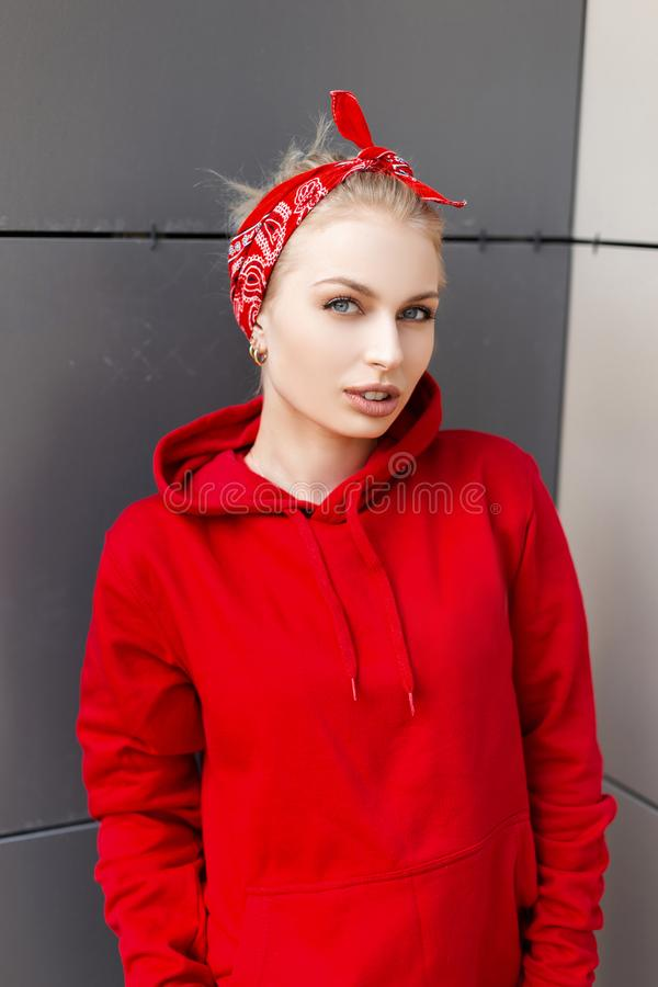 Modern cute young woman with natural make-up with blond hair in an American red bandana in a trendy hooded hoodie posing. Near a gray vintage wall in the city stock photography