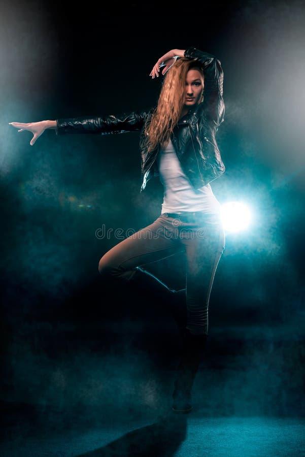 Modern dam som utför dans på etappen i strålkastare royaltyfria foton