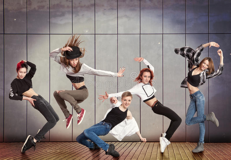 Modern dancing group practice dancing in front wall stock images