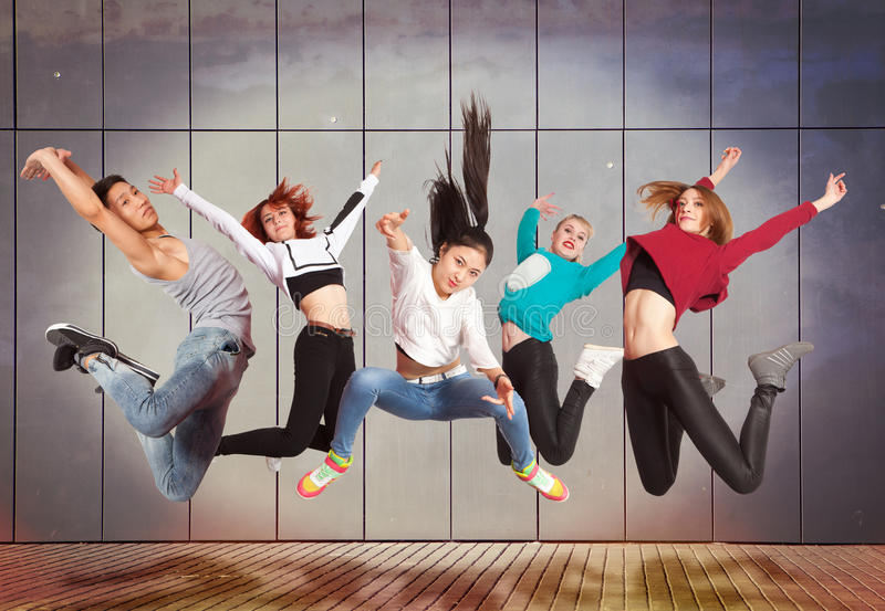 Modern dancing group practice dancing in front wall stock image