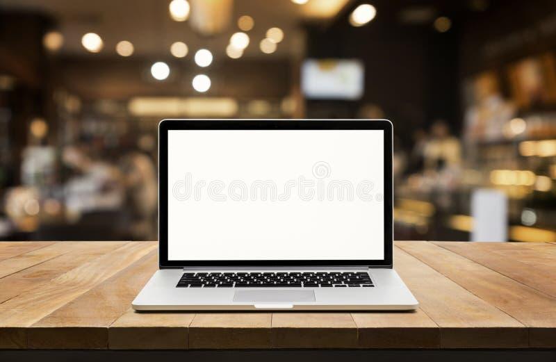 Modern dator, bärbar dator med den tomma skärmen på tabellen med suddighetskafét royaltyfri fotografi
