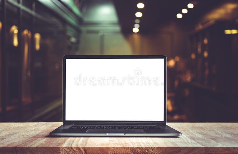 Modern dator, bärbar dator på räknarestång med suddighetskafét, restaurang royaltyfria bilder