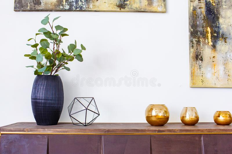 Modern decor concept. Black vase and glass candle pots on wooden board stock photo