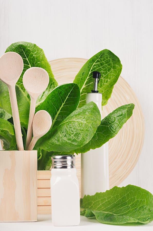 Modern dekor för kök - beige trämaträtt, skedar, gräsplansidor på vit wood bakgrund för mjukt ljus royaltyfri foto