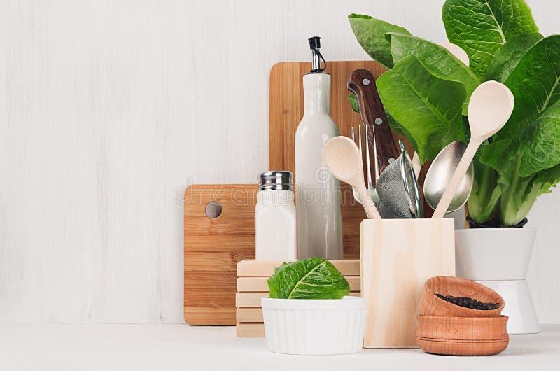 Modern dekor för kök - beigea träredskap, bruna skärbrädor, grön växt på vit wood bakgrund för mjukt ljus arkivfoton