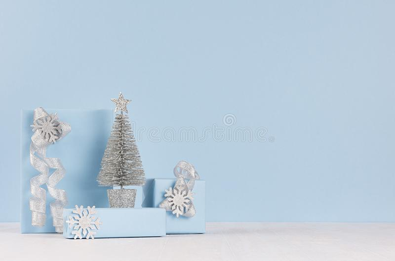 Modern delicate christmas background with copy space - silver tree and various festive gift boxes with sparkles ribbons in soft. Modern delicate christmas royalty free stock image