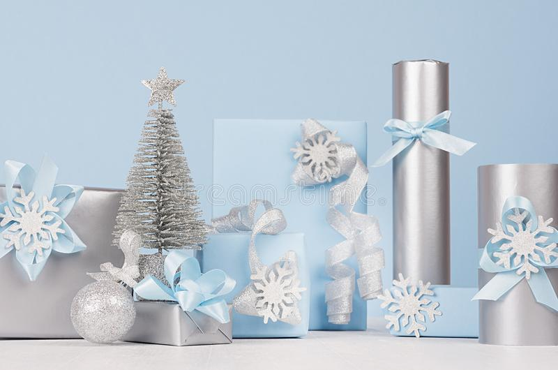 Modern delicate New Year background - silver tree and various festive pastel blue and metallic gift boxes with sparkles ribbons. royalty free stock images