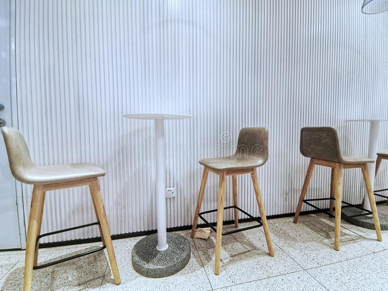modern design chairs and tables against white wall stock image