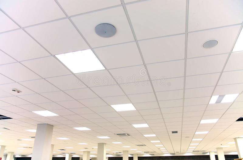 White office ceiling with white tiles and lighting stock photo