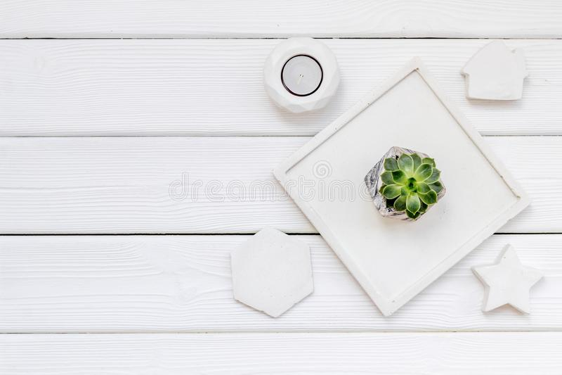Modern design of work desk with plant, candle, house and star figures on white wooden background top view copy space. Home decoration. Modern design of work desk royalty free stock photos