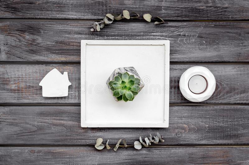 Modern design of work desk with plant, house figures on wooden background top view. Home decoration. Modern design of work desk with plant, house figures on stock photos