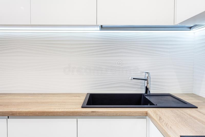 Modern designer chrome water tap over black new kitchen sink. The working area of the kitchen surface is made of wood. Table top m stock photography