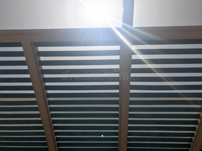 Modern designer roof in the open air with holes of beams with boards against the sun stock photo