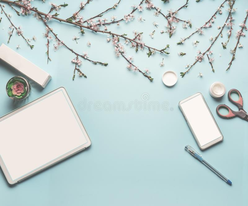 Modern desktop workplace flat lay with mock up of tablet computer and smart phone, cosmetic products, spring blossom stock photo