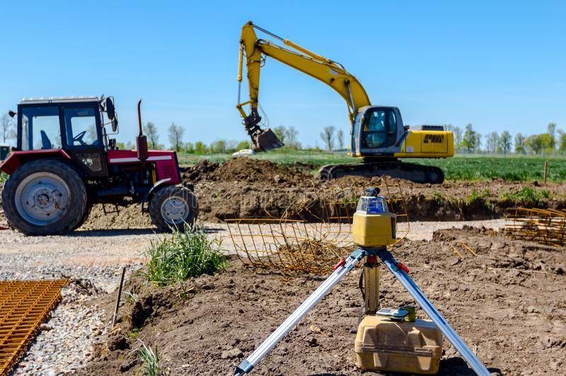 Modern device makes topographic measurements with laser, total center. Total center device with laser for leveling other devices to level construction site royalty free stock photography