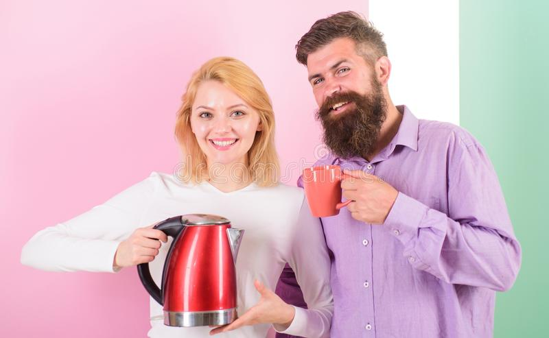 Modern devices make our life easier. Spending good morning together. Couple prepare morning drink electric kettle device. Electric kettle boils water very stock photo