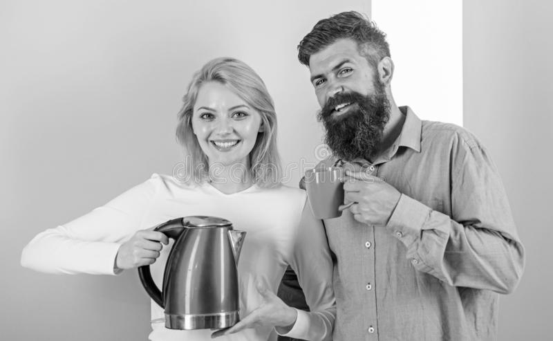 Modern devices make our life easier. Spending good morning together. Couple prepare morning drink electric kettle device. Electric kettle boils water very royalty free stock image