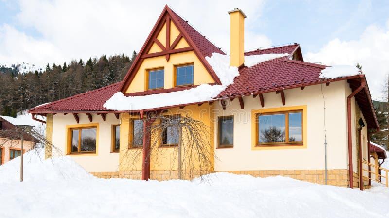 Modern die familiehuis in sneeuw wordt behandeld stock fotografie