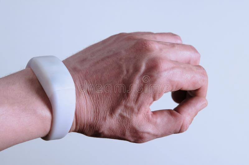 Modern digital device on a man`s hand. White bracelet like a smart watch or remote control. Gadget pixmob for parties, concerts,. Modern digital device on a man` stock photo