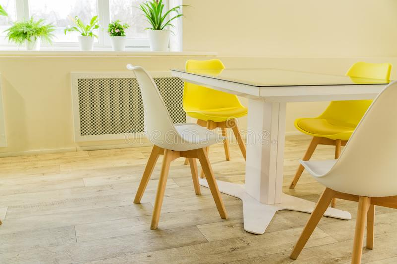 Modern dining room designed in scandi style. Glass table and yellow and white chairs.  stock photos