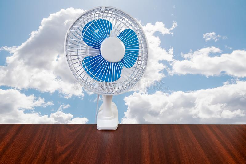 Modern domestic electric clamp desk fan against of sky. Modern domestic electric table fan with holder in the form clamp attached to the table on a background of royalty free stock photography