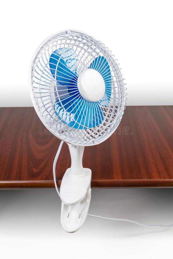 Modern domestic electric clamp desk fan attached to the table. Modern domestic electric table fan with holder in the form clamp attached to the wooden table on a stock image